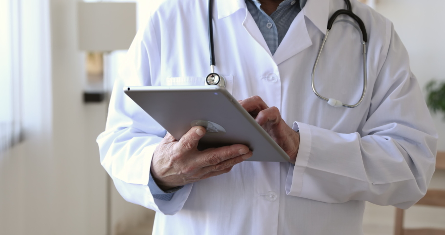 Close up middle aged older male doctor in white uniform holding digital computer tablet in hands, managing patients visits. Mature physician checking health history data in gadget, using modern app.