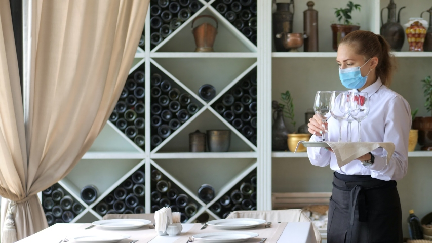 A waiter in a medical protective mask serves the table in the restaurant Royalty-Free Stock Footage #1054713455
