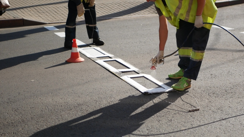 People draw the road. A road worker paints a zebra with a hand tool. Road marking. Workers and paint sprayers for roads. Thermoplastic paint for road marking. Royalty-Free Stock Footage #1054714217