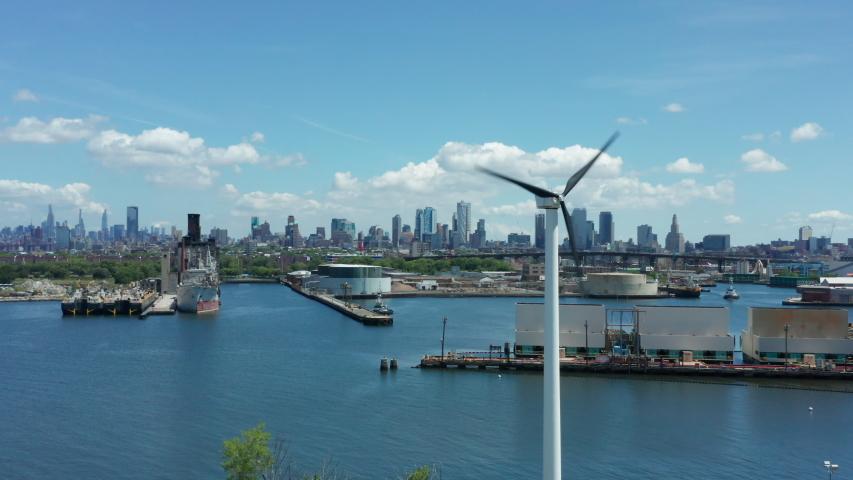 Flying counter clockwise around wind turbine revealing NYC skyline | Shutterstock HD Video #1054714763
