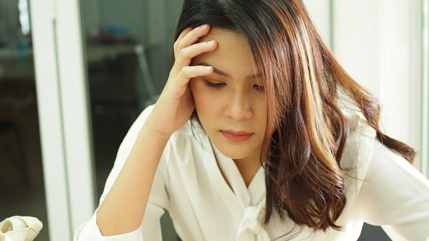 Young woman working in the office. Businesswoman tired and stressed with overworked. woman asian with worried not idea. freelance and business concept. | Shutterstock HD Video #1054715261