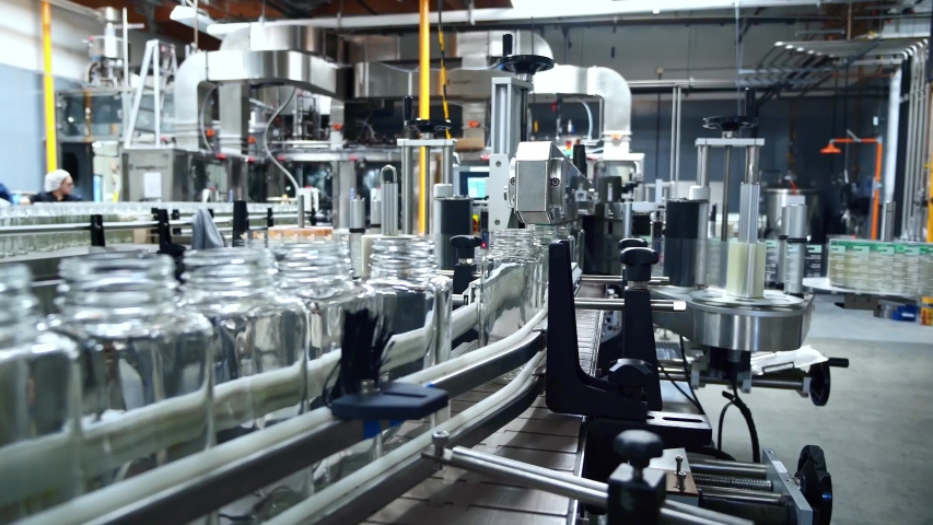 Beverage factory interior. Conveyor with glass bottles for juice or water. Modern equipment. Robotic automation line. packaging warehouse & processing facility.  Royalty-Free Stock Footage #1054715381