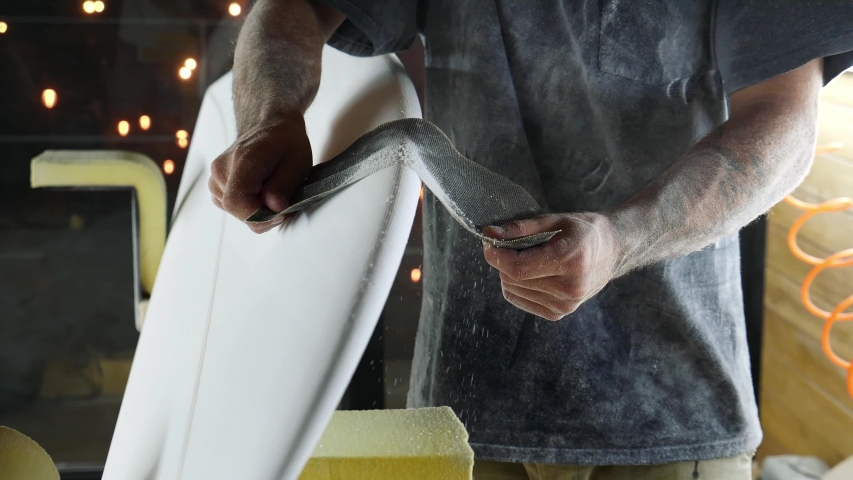 Surfboard manufacturing, Shaper is shaving rails on a surfboard. Concept of small business owner, skilled professional, occupation & job in America.