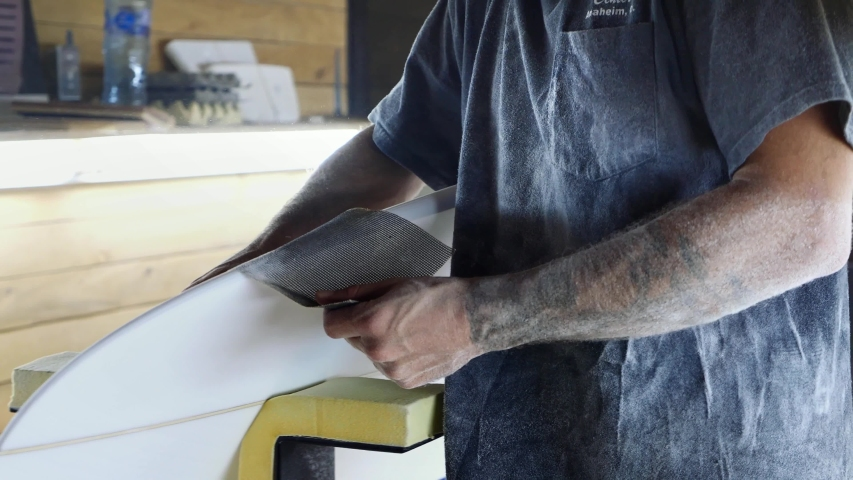 Surfboard making, Shaper is shaving rails on a surfboard. Concept of craftsmanship, small business in America, craftsman at work.