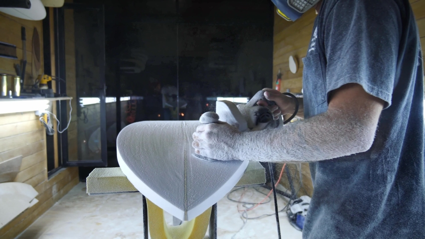 Surfboard manufacturing, Shaper sanding the bottom of the surfboard. Concept of small business owner, skilled professional, occupation & job in America.