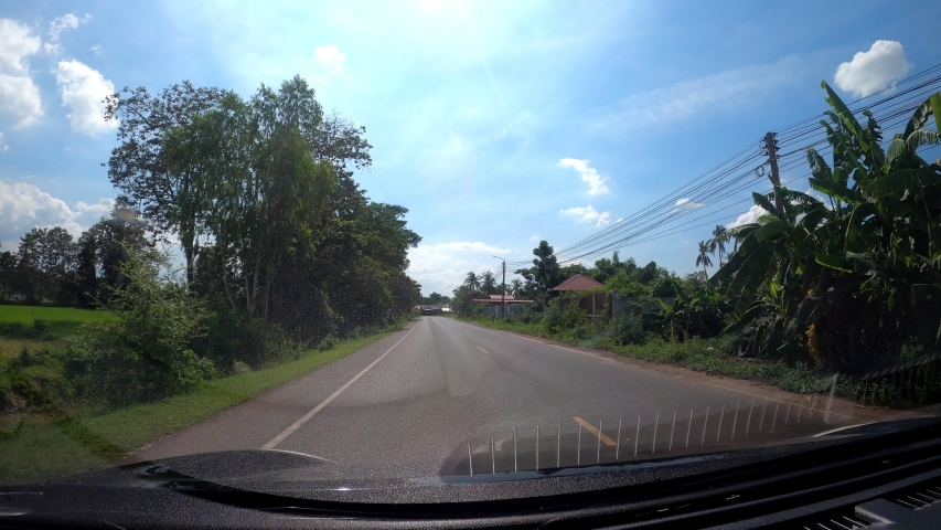 Driving a car on a rural highway in Thailand where people live and travel.