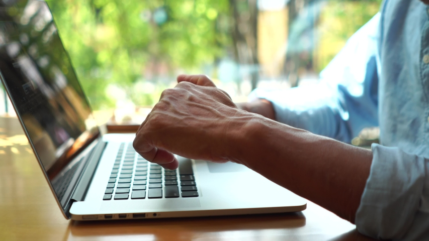 Close up hand old man using laptop typing working in cafe. | Shutterstock HD Video #1054716119