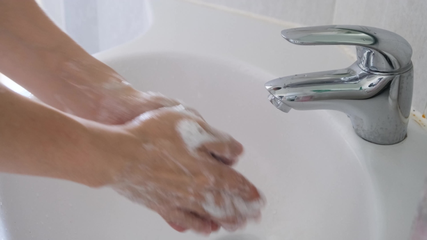 Hands of woman wash their hands in a sink with foam to wash the skin and water flows through the hands. Concept of health, cleaning and preventing germs and coronavirus from contacting hands | Shutterstock HD Video #1054716227