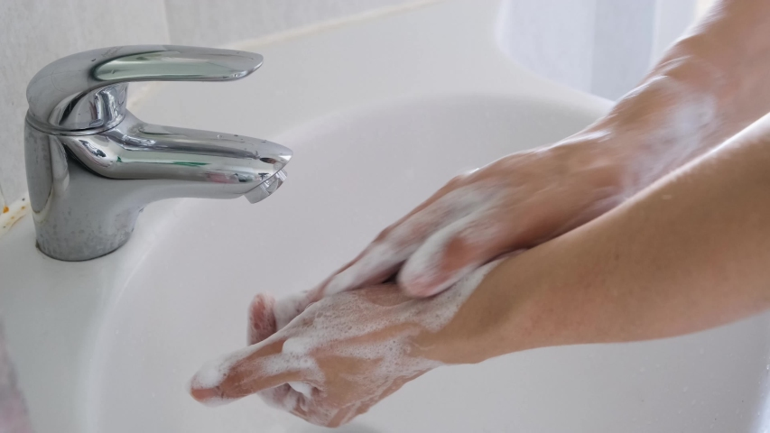 Hands of woman wash their hands in a sink with foam to wash the skin and water flows through the hands. Concept of health, cleaning and preventing germs and coronavirus from contacting hands | Shutterstock HD Video #1054716236