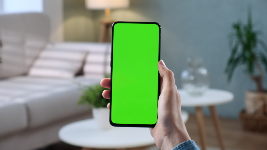 Handheld Camera: Point of View of Woman at Phone with Green Screen for Copy Space. Chromakey 20s Lady Watching Video News on Couch Close up. Tap to Click on Centre of Screen
