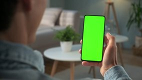 Handheld Camera: Back View of Brunette Man Holding Chroma Key Green Screen Smartphone Watching Content Without Touching or Swiping. Boy Using Mobile Phone, Browsing Internet, Watching Content,