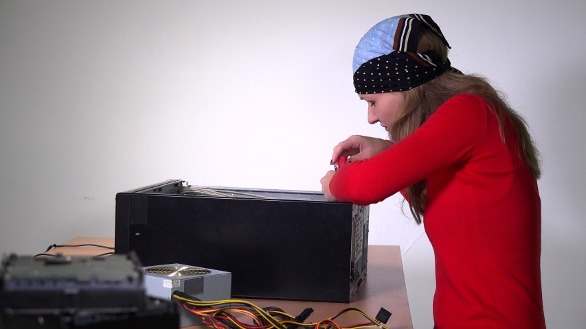 Technician girl remove motherboard from desktop computer and examine it. White wall background. Static shot. 4K | Shutterstock HD Video #1054716566