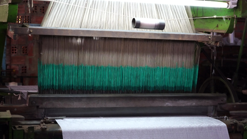 Working spin machine in a cloth silk factory, close up. Factory for the production of silk threads and fabrics near Dalat, Vietnam | Shutterstock HD Video #1054716611
