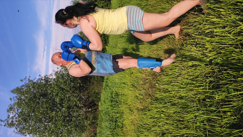 Man and woman in the summer in the park are engaged in Thai boxing with gloves. Vertical