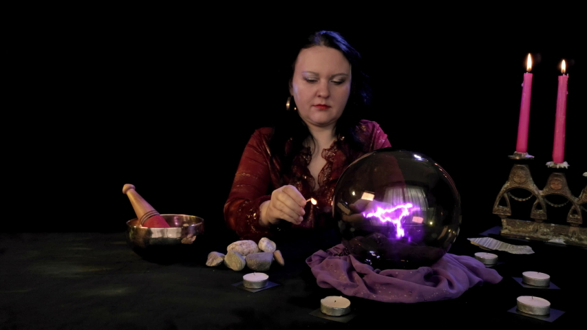 A fortuneteller in a magic salon lights candles on a black background behind magic fire | Shutterstock HD Video #1054716782