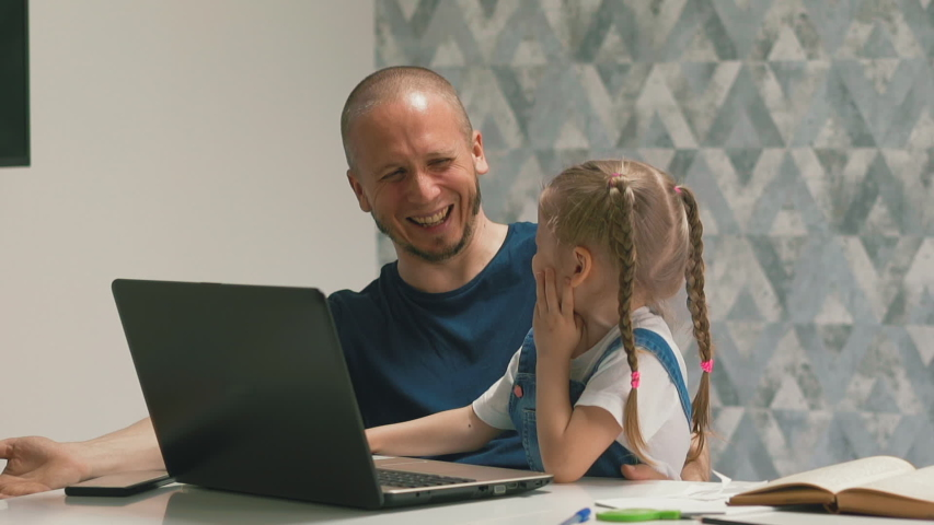 Closeup slow motion of daddy on his lap sits little daughter with pigtails, home learning, video conference link with teacher, they laugh, smile each other, child happily presses buttons on keyboard   Shutterstock HD Video #1054717205