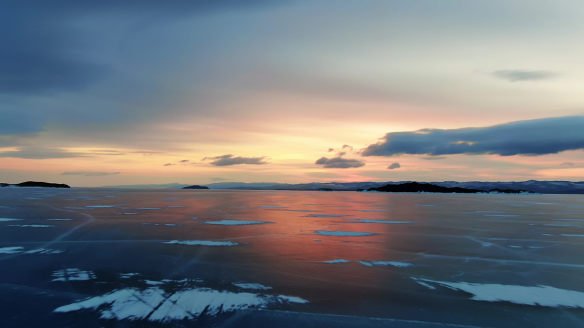 Northern landscape frozen lake drone flying down with beautiful reflection on ice at sunset 4K. Amazing winter Baikal with red sunrise. View drone flight on north frost lake. Natural reflection sunset | Shutterstock HD Video #1054717268