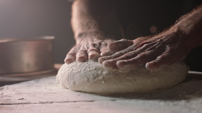 Closeup shot of hands of senior bakery chef applying flour on dough, old man kneading dough, making bread using traditional recipe, isolated on black background 4k footage