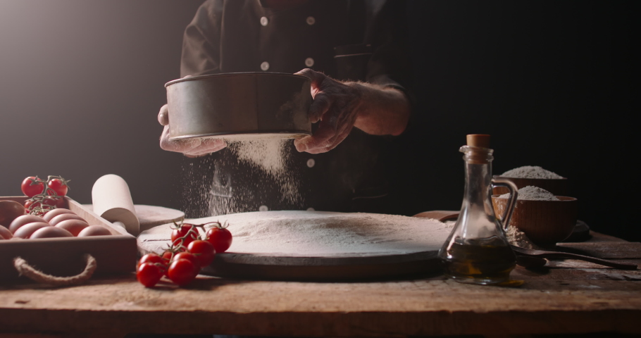 Closeup shot of experienced italian bakery chef sifting flour through sieve, starting to make pizza with traditional methods, isolated on black background 4k footage | Shutterstock HD Video #1054717553