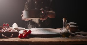 Closeup shot of experienced italian bakery chef sifting flour through sieve, starting to make pizza with traditional methods, isolated on black background 4k footage