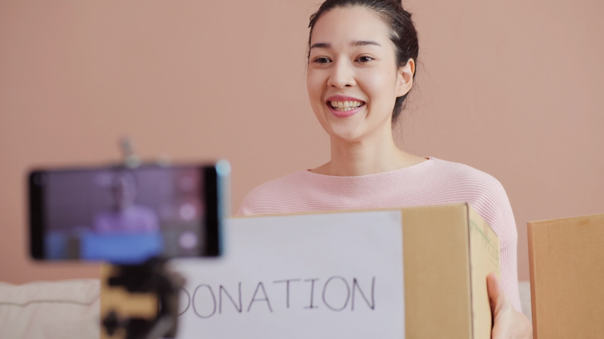 Beautiful asian woman talking with camera for broadcast and live video to invite people to donate things to the poor people. | Shutterstock HD Video #1054717664