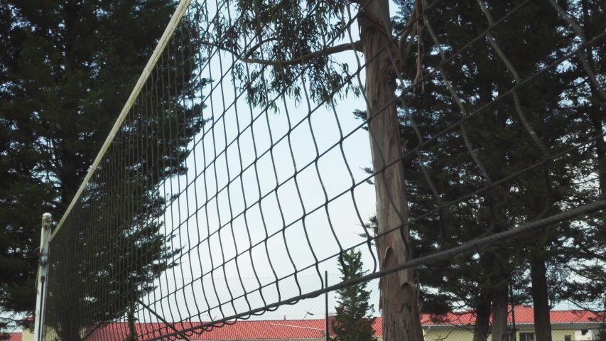 Close-up volleyball net with white support posts on a sports ground with tall trees and buildings in the distance | Shutterstock HD Video #1054718708
