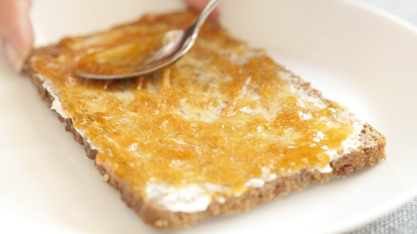 Breakfast preparing with butter and jam spread over bread 4K video | Shutterstock HD Video #1054718975