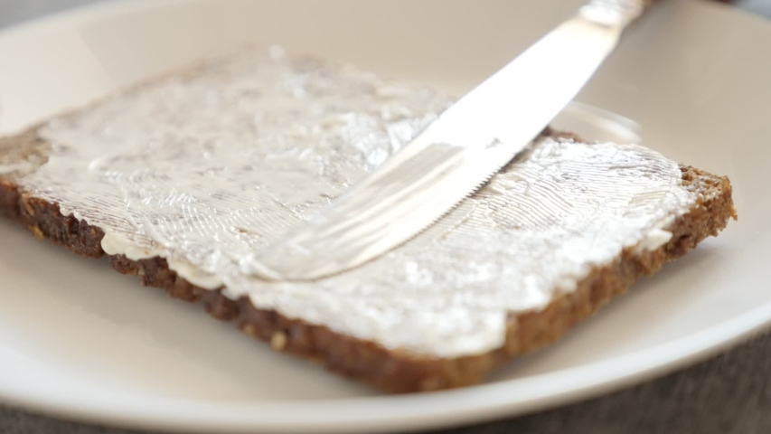 Slow motion knife spreading butter over the bread surface close-up video | Shutterstock HD Video #1054718984