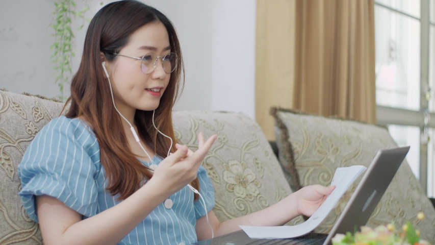Serious Asian woman distance student online wear headphone conferencing on laptop communicate by video call explain course help e learning computer education concept. Distancing working online at home Royalty-Free Stock Footage #1054718987