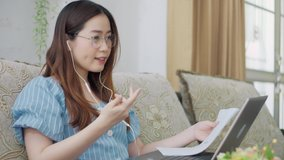Serious Asian woman distance student online wear headphone conferencing on laptop communicate by video call explain course help e learning computer education concept. Distancing working online at home