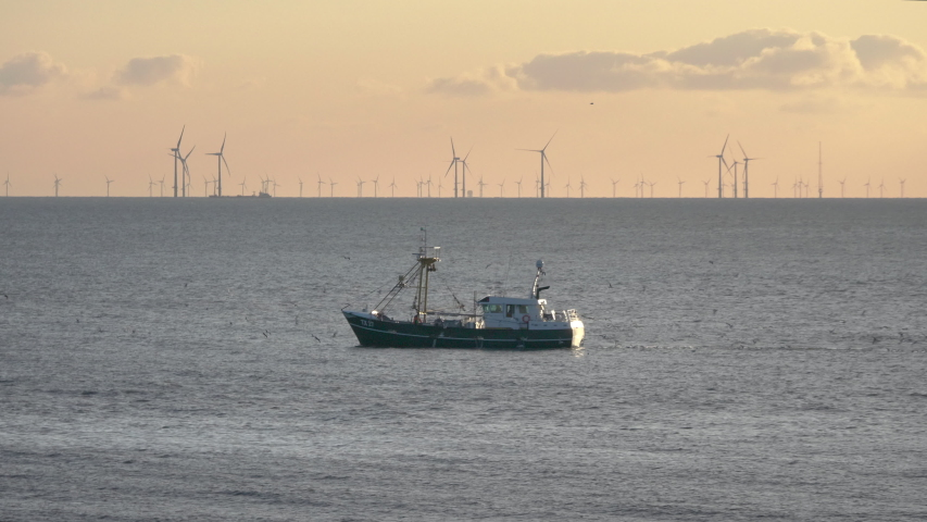 Fishing boat on the north see coast with wind turbines on the background Royalty-Free Stock Footage #1054719101