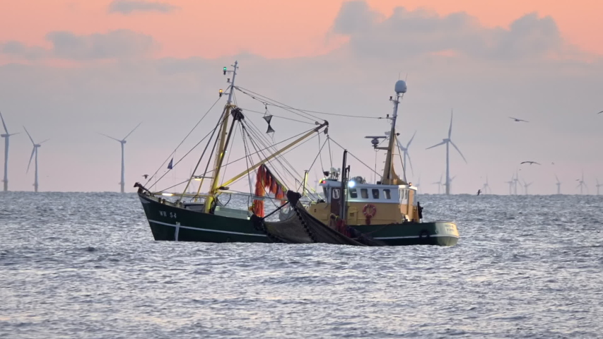 Trawler on the north see coast with wind turbines on the background. Slow motion. Royalty-Free Stock Footage #1054719104