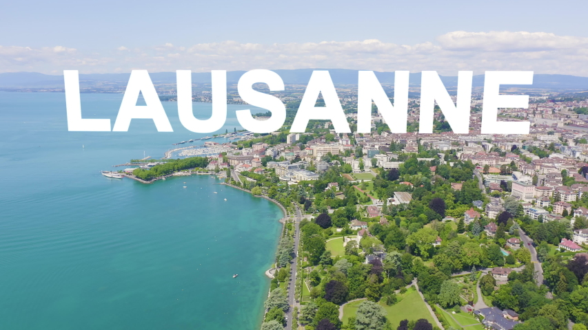 Inscription on video. Lausanne, Switzerland. Flight over the central part of the city. The coast of Lake Geneva. Glitch effect text, Aerial View