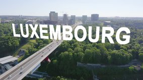 Inscription on video. Luxembourg, Avenue John F. Kennedy, An area with modern skyscrapers. Pont rouge. Glitch effect text, Aerial View