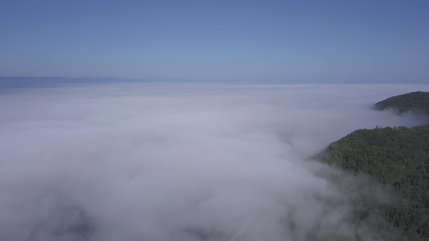 D-Cinelike. Flying above the clouds. Coast of Lake Baikal. Mountains covered with forest. Russia, Aerial View