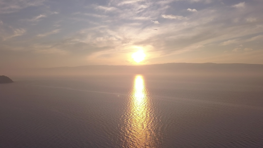 D-Cinelike. Russia, Lake Baikal, Olkhon Island, Sunset over Small Sea Bay, Aerial View, Departure of the camera
