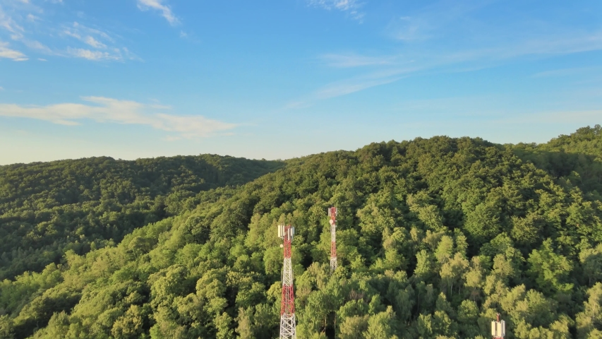 Backwarding aerial over dense green mountains with Five G telecommunication towers standing tall on bright sunny day. | Shutterstock HD Video #1054719482