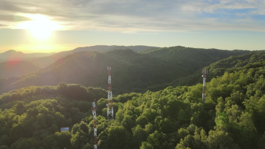 Rotating aerial view of 5G telecommunication towers standing tall on dense green mountains against beautiful sunlight | Shutterstock HD Video #1054719491