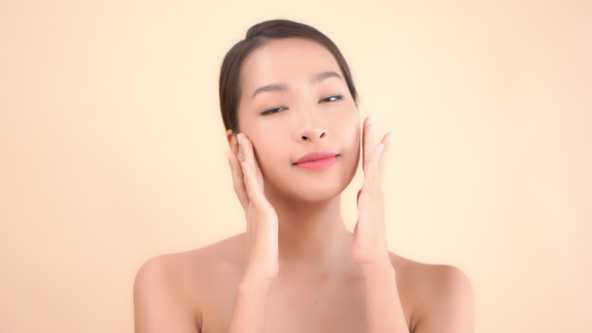 A young beautiful Asian woman massages her face gently with her fingertips. | Shutterstock HD Video #1054719536