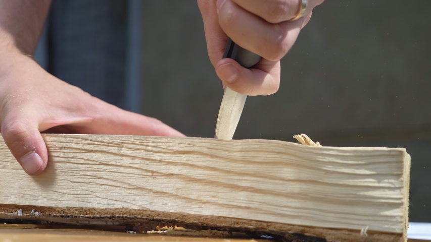 Closeup. man cuts out patterns with a knife on a wooden board, outdoors. | Shutterstock HD Video #1054719761