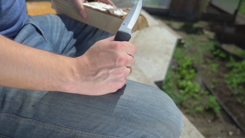 Closeup. man cuts out patterns with a knife on a wooden board, outdoors. | Shutterstock HD Video #1054719848
