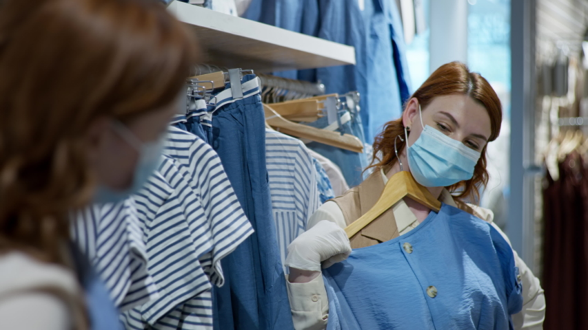 Happy girl in medical mask and gloves chooses new clothes on shopping field removing carnitine and opening retail shop | Shutterstock HD Video #1054721006