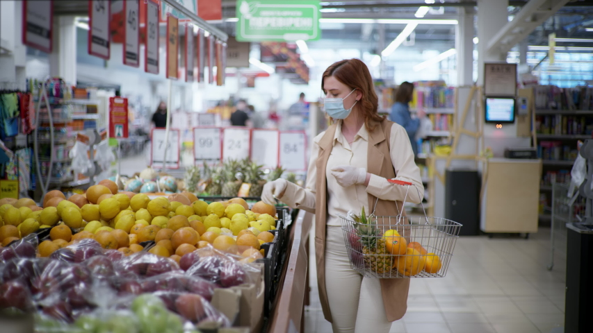 purchases coronavirus, attractive female shopper in medical mask and gloves with shopping basket picks fruits in a supermarket during a pandemic on isolation Royalty-Free Stock Footage #1054721015