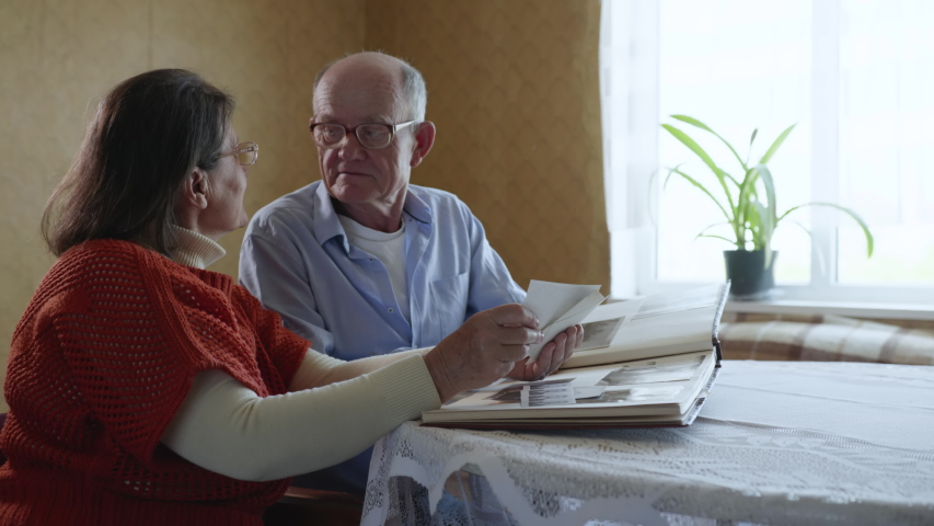 Joyful married couple old men and women rejoice and laugh enjoying family memories looking at photos in photo album sitting in room at a table