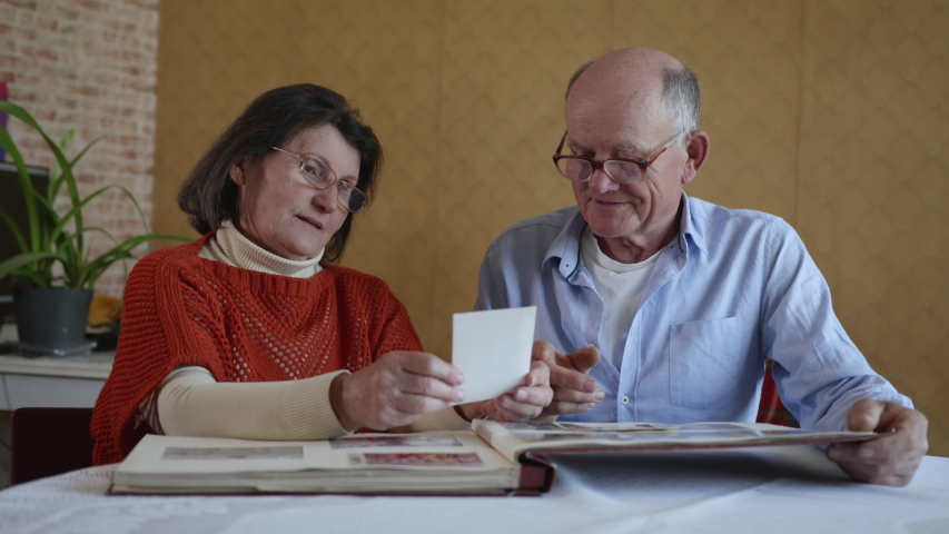 Family memories, a cheerful married couple an elderly man and woman enjoy memories flipping through an old family album with photos sitting at a table