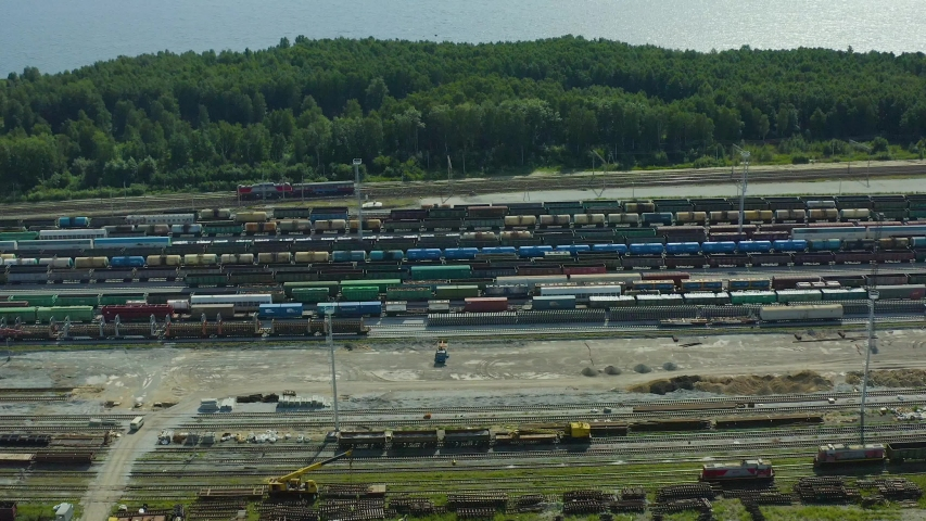 Railway tracks with freight trains, a locomotive with cars passing in the background. View from drone. | Shutterstock HD Video #1054721174