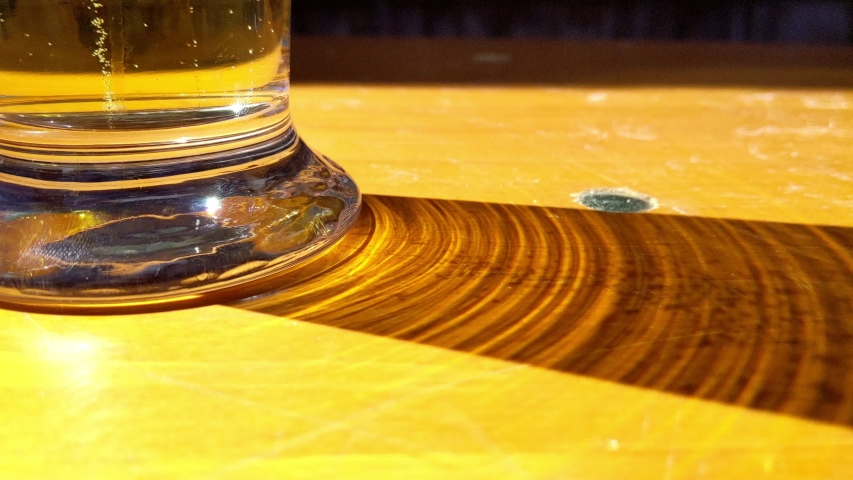 Glass of carbonated beer casting shadow on wooden table. Carbonic acid bubbles are visible in the glass and in the shadow | Shutterstock HD Video #1054721207