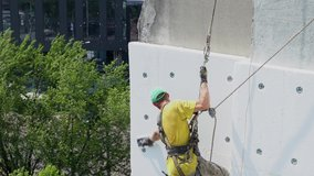 Closeup view video of facade of wall of building. Part of fresh construction of external wall thermal insulation. Work at heights concept. Worker doing his hard job.