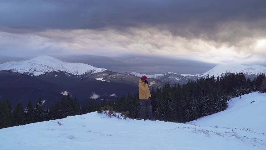 A man travels in the mountains in winter. A traveler talks on the phone in the mountains in winter. Carpathian mountain range. The concept of travel and active lifestyle. 4K   Shutterstock HD Video #1054722407