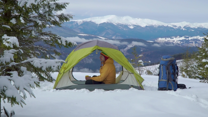 Tourist in a tent in in the mountains in a winter. A man is resting and drinking tea from a yellow mug. Beautiful winter landscape. Travel concept. 4K | Shutterstock HD Video #1054722413
